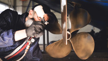 The Yacht Technician Cleans The Propeller Using A Chemical Spray (paint) Cleaner From Dirt. Concept From: New Technique, Chemistry, Profesional, Paint, Respirator, Mask, Yacht Club.