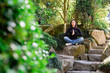 Beautiful woman meditating in Japanese garden.