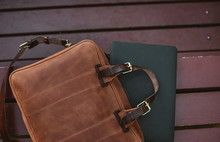 Close Up Of Laptop With Leather Briefcase On A Wooden Background