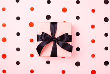Pink Gift Box With Black Bow On Pink Background With Red And Black Polka Dots. Holiday Or Black Friday Concept.