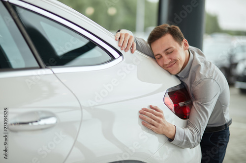 Close up of adult content caucasian man being completely satisfied with his new car, hugging it with eyes closed and leaning on car bonnet