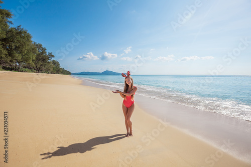 Poster Zanzibar Happy young woman with long hair in red swimsuit wearing funny christmas reindeer antlers holding something imaginary standing on the beach by the sea with blue water and sky on Phuket island,Thailand