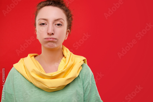Fotografía  Beautiful young female teenager in stylish clothes sends an air kiss while looking into the camera on a red isolated background
