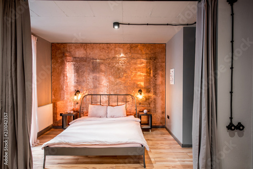 Fototapeta Modern loft bedroom interior with wall made of copper metal. Real photography obraz