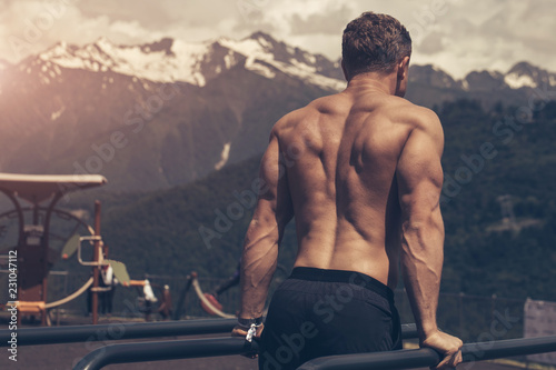Fotografiet  Rear view of a young athletic half naked man doing push ups on parallel bars outdoors