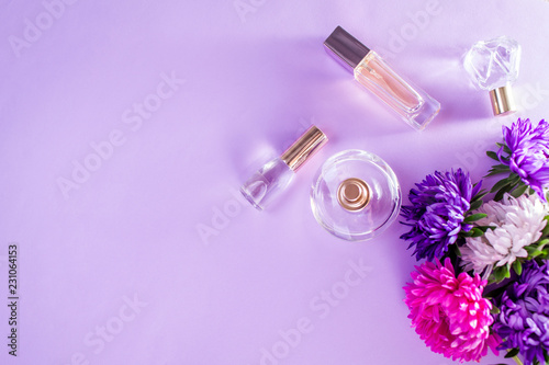Fototapeta Bottles of perfume with purple and white flowers obraz