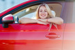 canvas print picture - Photo of happy blonde woman sitting in red car with open window