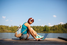 Image Of Woman With Headphones In Headphones With Backpack And Laptop In Hands Sitting On Bank Of River