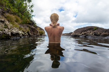 Rear View Of Beautiful Naked Woman Bathing And Relaxing In Natural Swimming Pool Before The 500 Feet Waterfall In Natural Park On Tropical Island Of Mauritius.