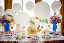 Candy Bar On Golden Wedding Party With A Lot Of Different Candies, Cupcakes, Souffle And Cakes. Decorated In Brown And Purple Colors, Nature And Eco Theme, Indoor
