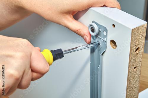 Photo Furniture assembler tightens screw in drawer slides.