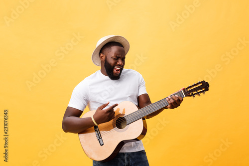 Muscular black man playing guitar, wearing jeans and white tank-top. Isolate over yellow background. - 231076348