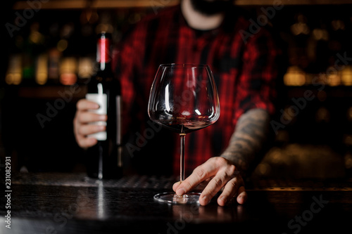 Foto op Canvas Alcohol Barman with an empty burgunya glass and a bottle of red wine