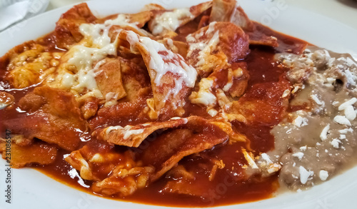 Fotografía Delicious chilaquiles, typical Mexican food with beans, cheese and hot tomato sauce over traditional tortilla