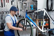 Professional Mechanic Repairing Bicycle In Modern Workshop