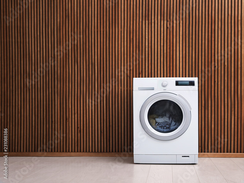 Fotografie, Obraz  Washing machine with laundry near wooden wall. Space for text