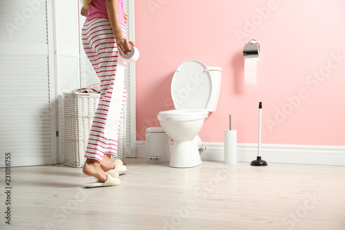 Woman with toilet paper roll standing in bathroom at home Wallpaper Mural