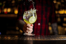 Bartender Making Splash Of A Gin Tonic Cocktail Decorated With Lime Slices