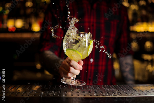 Photographie Bartender making splash of a Gin Tonic cocktail with lime slices