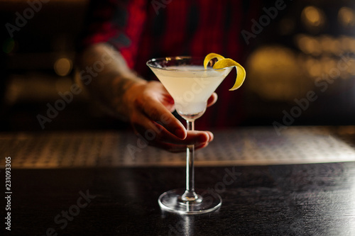 Bartender serving a White Lady cocktail decorated with orange zest
