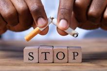 Man Breaking Cigarette Over Wooden Stop Blocks