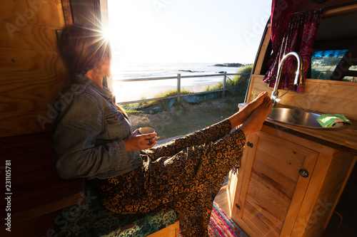 Canvas-taulu Young woman in camper van watching summer sunrise while drinking coffee by the b