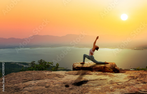 plakat Woman practice yoga on mountain with sunset or sunrise background