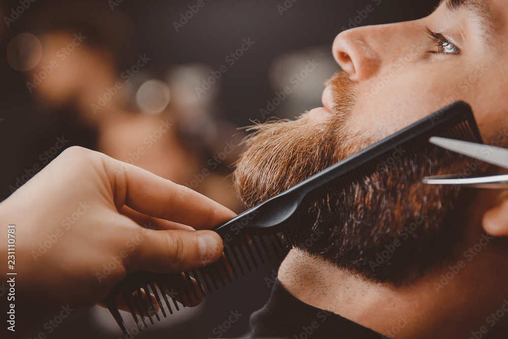 Fototapeta Hipster man sitting in armchair barber shop while hairdresser shaves beard with scissors.