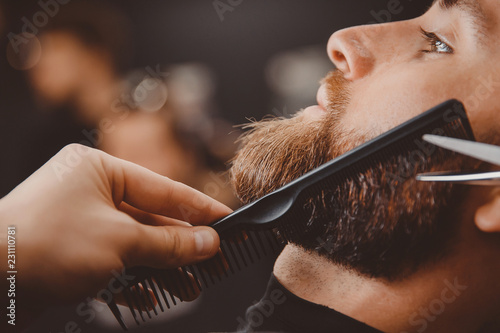 Foto Hipster man sitting in armchair barber shop while hairdresser shaves beard with scissors