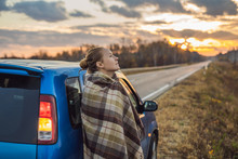 A Woman In A Plaid Stands By The Car On The Side Of The Road In The Background Of The Dawn. Road Trip Concept