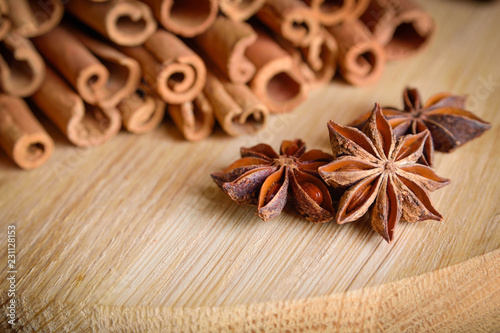 Photo shelves of cinnamon and anise stars in dark backgrounds on a wooden background