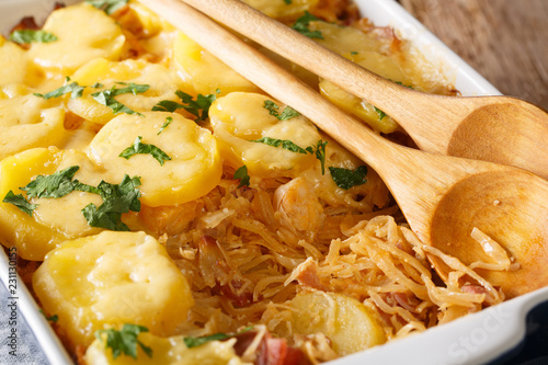 Tableau sur Toile Freshly cooked sauerkraut casserole with potatoes, bacon and cheese close-up