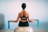 Young sporty attractive woman practicing pilates with resistance bands back sitting on fitness balls on white urban studio. Yoga and Pilates lifestyle healthy concept.