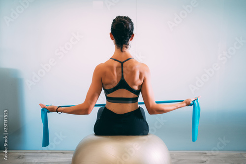 Young sporty attractive woman practicing pilates with resistance bands back sitting on fitness balls on white urban studio Tablou Canvas