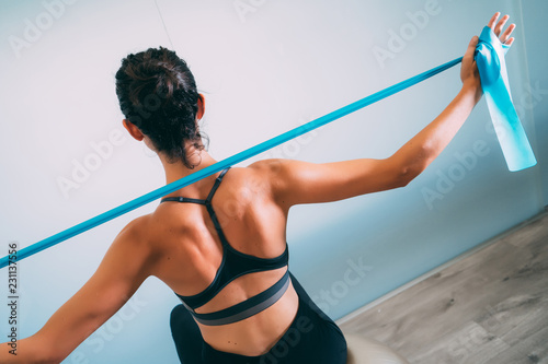 Fototapeta Young sporty attractive woman practicing pilates with resistance bands on white urban studio. Yoga and Pilates lifestyle healthy concept. obraz