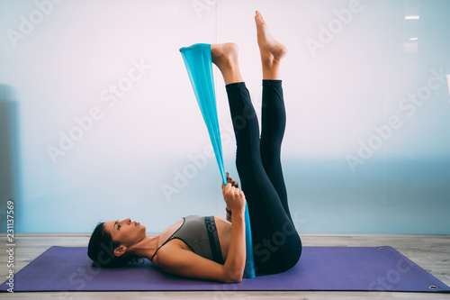 Obraz Young sporty attractive woman practicing pilates with resistance bands on white urban studio. Yoga and Pilates lifestyle healthy concept. - fototapety do salonu