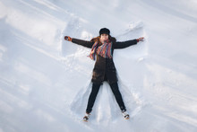 A Young Caucasian Girl On The Snow Shows An Angel. Spreading Arms. Top View. Drone. Smile. Happy.