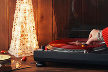 A Young Woman In A Red Knitted Winter Pullover Puts A Black Vinyl Record On A Turntable, A Stylus A Needle And Listens To Music Against The Background Of A Glowing Christmas Tree And A Cozy New Year's