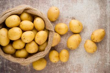 Fototapeta Sack of fresh raw potatoes on wooden background, top view.