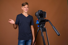 Studio Shot Of Young Handsome Teenage Boy Against Brown Backgrou