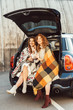 laughing adult women wrapped in blankets holding soda bottles sitting in car trunk at urban street