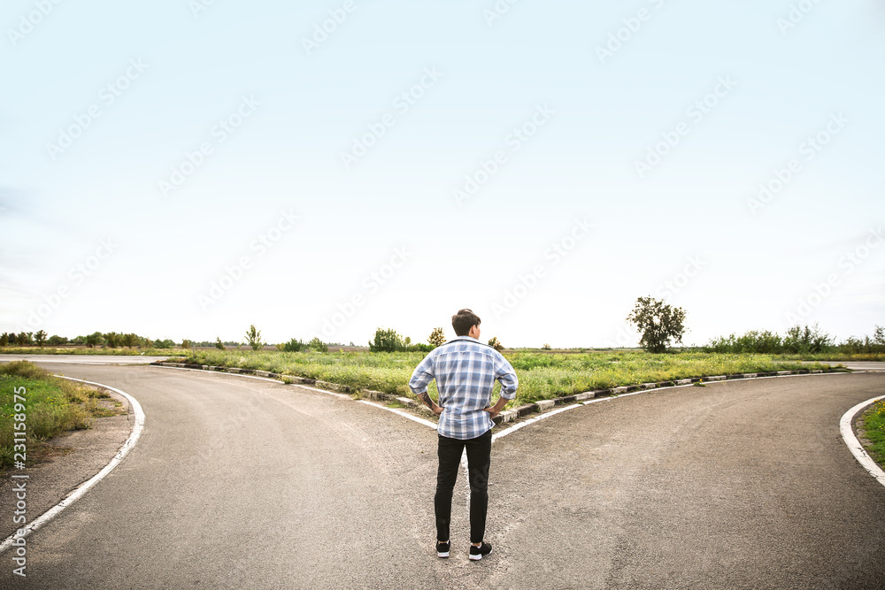 Fototapety, obrazy: Young man standing at crossroads. Concept of choice