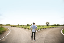 Young Man Standing At Crossroads. Concept Of Choice
