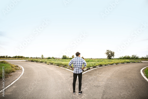 Fototapeta Young man standing at crossroads. Concept of choice