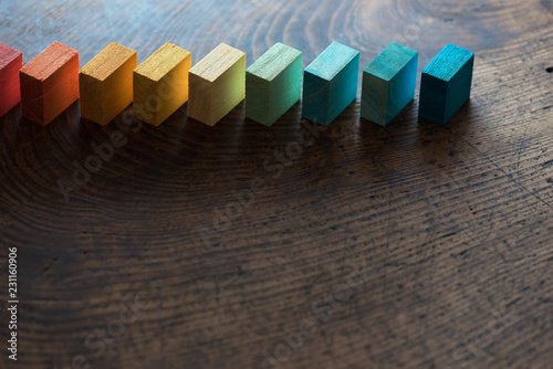Colored wooden blocks diagonally aligned on old vintage wooden table Wallpaper Mural