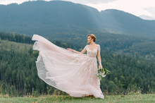 Whirling Bride Holding Veil Skirt Of Wedding Dress At Pine Forest