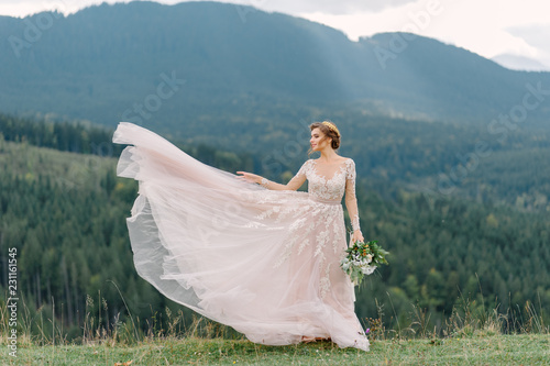 Canvas whirling bride holding veil skirt of wedding dress at pine forest
