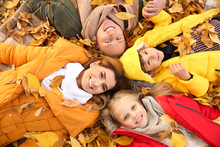 Happy Family Lying On Dry Leaves In Autumn Park