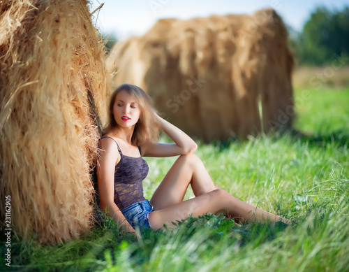 Photo  Sexy woman in blue denim shorts and black lingerie near to a haystack