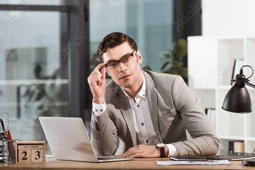 Fototapety, obrazy: handsome businessman with eyeglasses sitting at workplace in office and looking at camera